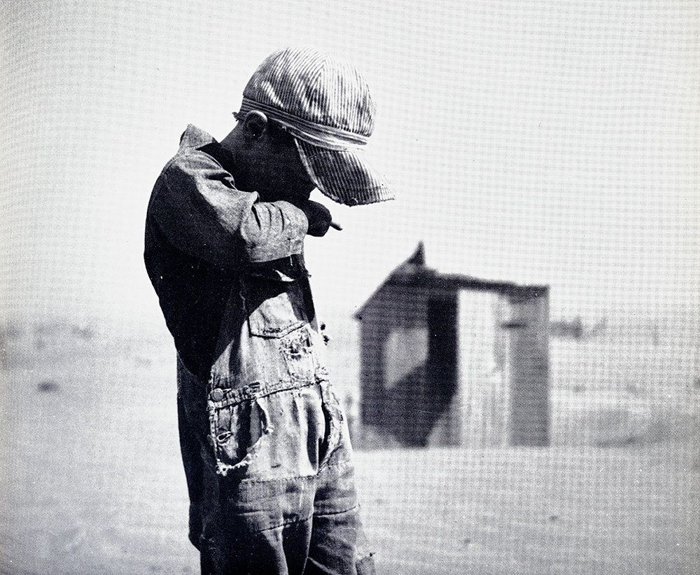 Photograph of a farm boy in a dust storm